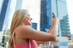 Young woman with smartphone photographing city. Women and people concept - happy smiling young woman with smartphone photographing city Royalty Free Stock Photos