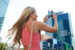 Young woman with smartphone photographing city stock photo