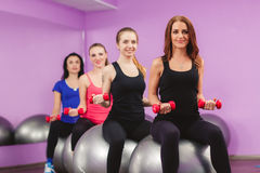Women perform exercises with a large ball for fitness. Royalty Free Stock Images