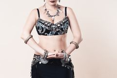 Women performs belly dance in ethnic dress on beige background royalty free stock photo