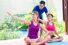 Women and personal trainer at fitness exercise stock images