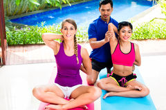 Women and personal trainer at fitness exercise stock image