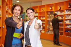 Women in pharmacy holding thumbs up Stock Photography