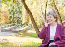 women with phone in autumn park Stock Photo