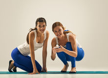 Women with phone. yoga in pair Stock Photography