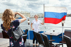 Women photographing with Russian flag on ship deck Royalty Free Stock Photography