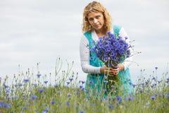 Women picking blue flowers Stock Photo