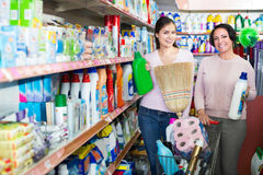 Women picking bottles with detergent. Two positive women picking bottles with detergent from shelf in supermarket Royalty Free Stock Photos