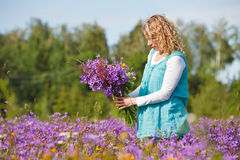 Women picking lilac flowers Stock Images