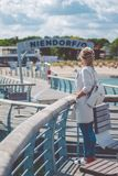 Women on pier near beach with roofed wicker chairs in Travemuende at the Baltic Sea. Travepromenade in Travemunde, a Royalty Free Stock Photography