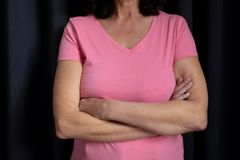 women in pink for breast cancer focus on crossed arms stock image