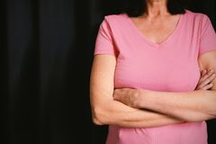 women in pink for breast cancer focus on crossed arms royalty free stock photography