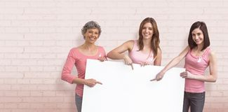 Composite image of women in pink outfits holding board for breast cancer awareness. Women in pink outfits holding board for breast cancer awareness against white stock images