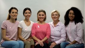 Women with pink ribbons aware of breast cancer, smiling into camera, health. Stock photo royalty free stock photography