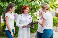 Women with pink ribbons looking at doctor with clipboard breast cancer awareness. Concept stock photo