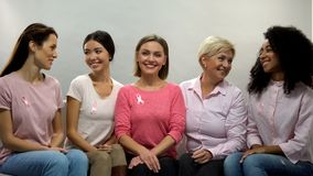 Women with pink ribbons sharing experience, national breast cancer awareness. Stock photo royalty free stock images