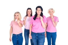 Women in pink t-shirts with ribbons. Women in pink t-shirts holding breast cancer awareness ribbons and smiling at camera isolated on white Royalty Free Stock Image
