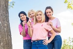 Women in pink t-shirts with ribbons. Women in pink t-shirts holding breast cancer awareness ribbons and smiling at camera Stock Images