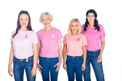 Women in pink t-shirts with ribbons. Cheerful women in pink t-shirts with ribbons standing together and smiling at camera isolated on white Royalty Free Stock Images
