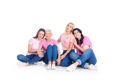 Women in pink t-shirts with ribbons. Sitting together and smiling at camera isolated on white Royalty Free Stock Image