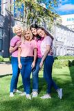 Women in pink t-shirts with ribbons. Standing together and smiling at camera Royalty Free Stock Photography