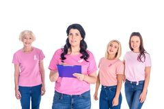 Women in pink t-shirts with ribbons. Woman writing on clipboard while smiling women in pink t-shirts with ribbons standing behind and looking at camera isolated Stock Photo