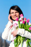 Women with pink tulips talking by a cellular Stock Photography