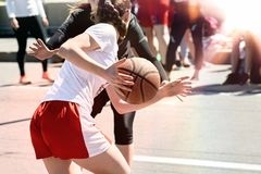 Women play basketball. Group of happy teenage girls in sports uniform, playing basketball outdoors in the city stock photography