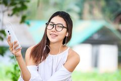 The women play phone in the park and wear white dress. She is smile and wear earphone. stock photography
