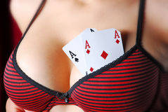 Women play poker. Card tucked in the breast Royalty Free Stock Images