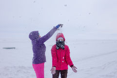 Women play in the snow during a snowfall on the ice of Lake Baik Royalty Free Stock Photos