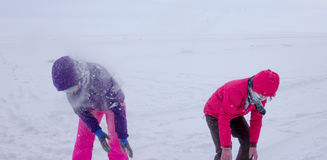 Women play in the snow during a snowfall on the ice of Lake Baik Royalty Free Stock Photography