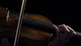 Women play strings of a violin in a dark room. Black background. Close up stock video footage
