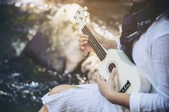 Women play ukulele new to the waterfall stock photos