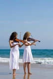 Women play violin on beach. Two beautiful young women play violins music on the beach Royalty Free Stock Images