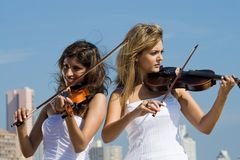 Women play violin on beach. Two beautiful young women play violins music on the beach Stock Images