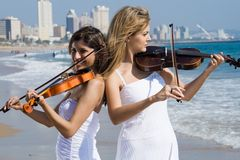Women play violin on beach. Two beautiful young women play violins music on the beach Stock Photos