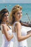 Women play violin on beach. Two beautiful young women play violins music on the beach Stock Photo