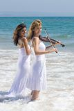 Women play violin on beach Royalty Free Stock Photography