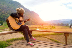 Women playing acoustic guitar in the rice field, ralax and lifestyle. Stock Image