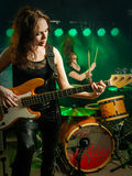 Women playing in the band. Photo of a female bass player and drummer of a rock band playing on stage Royalty Free Stock Images