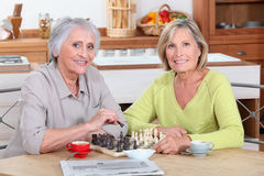 Women playing chess in kitchen Stock Image