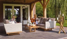 Women playing guitar on patio Stock Photo