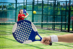 Women playing paddle tennis. Standing and swatting the ball on court royalty free stock photos