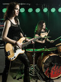 Women playing in the rock band. Photo of a female bass player and drummer of a rock band playing on stage Royalty Free Stock Photo