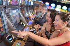 Women playing slot machine royalty free stock photo