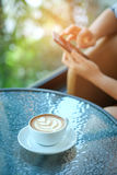 Women playing smart phone with coffee heart latte in hand put on Royalty Free Stock Image