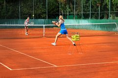 Women playing tennis outdoors Royalty Free Stock Photo