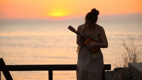 Women with ukulele. Women playing ukulele at the beach stock video footage