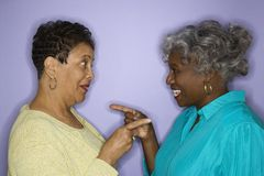 Women pointing at eachother. Stock Photo